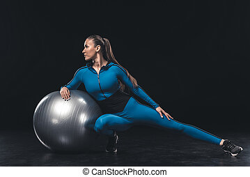 Athletic young woman in sportswear stretching with fitness ball