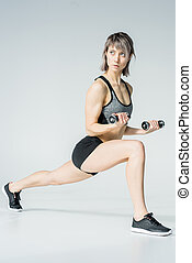 Athletic young woman in sportswear training with dumbbells