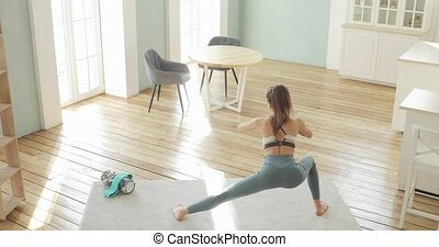Athletic young woman making squats for glutes in side lunge ...