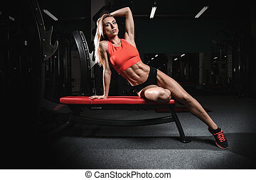 Athletic young woman posing and exercising fitness workout with weights