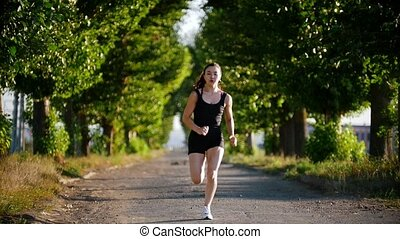 Athletic Young Woman Running In The Green Park