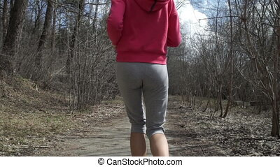 Athletic young woman running in the nature.