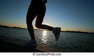 Athletic Young Woman Running On The Waterfront