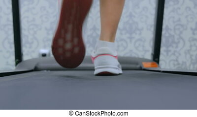 Athletic young woman running on treadmill at the gym