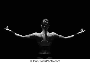Athletic young woman showing muscles of the back and hands...