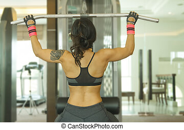 Athletic young woman training in fitness gym