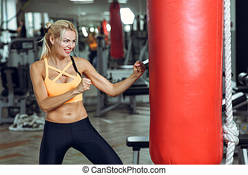 Athletic young woman training with punching bag at gym