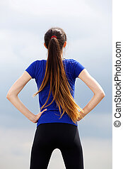 Athletic young woman with hands on hips - Portrait from ...