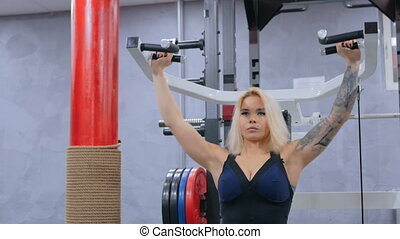 Athletic young woman working out on fitness exercise equipment