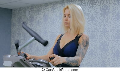Athletic young woman working out on stepper machine at the gym