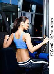 Athletic young woman works out on training apparatus