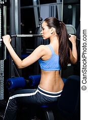 Athletic young woman works out on training gym equipment