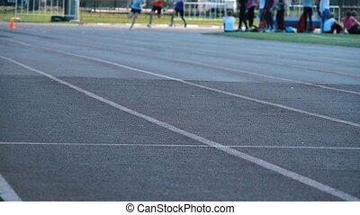 Athletics running in the stadium.