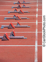 Athletics Starting Blocks on a red running track in the...