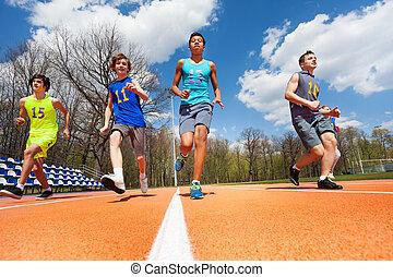 Athletics teenage boys running on the racetrack - Bottom...