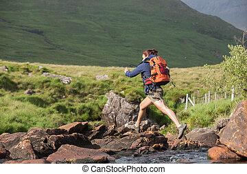 athletische, wanderer, springen, über, steinen