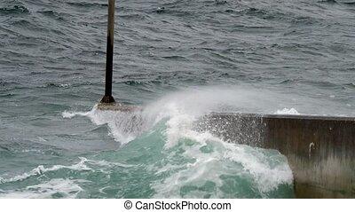 Atlantic ocean splashing waves against pier.