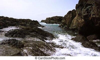 Atlantic ocean water and rocks - Waves moving through rocks,...