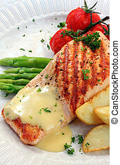 Meal of grilled atlantic salmon with potato wedges, roasted truss tomatoes, and hollandaise sauce.