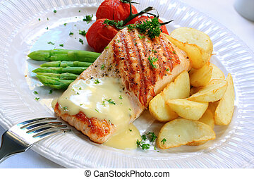 Meal of grilled salmon fillet, served with asparagus, potato wedges, truss tomatoes, and hollandaise sauce.