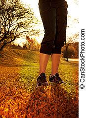 atleta, corredor, pies, estantes, en, pasto o césped, primer plano, en, shoe., mujer, condición física, salida del sol, empujoncito, entrenamiento, salud, concept.