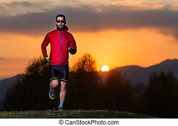 atleta, hombre, con, barba, carreras, en las montañas, durante, un, colorido, ocaso, de, fuego