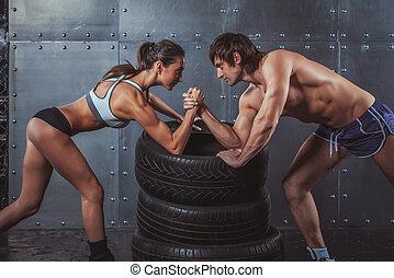 atleta, muscular, deportistas, hombre y mujer, con, manos agarraron, arme lucha, desafío, entre, un, pareja joven, crossfit, condición física, deporte, entrenamiento, estilo de vida, culturismo, concept.