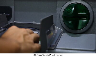 ATM close-up and the user's hand with a plastic card - ATM...