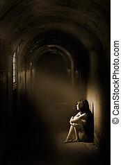 A beam of light shines onto a nude woman
