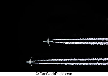 Two jet aircraft flying in a horizontal and parallel formation with smoke trails, set against a black sky background.