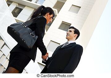 Atractive businessman and businesswoman shaking hands outside of office building. Couple working.