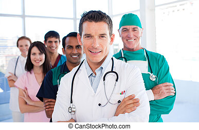Atractive doctor standing with his colleagues in a hospital
