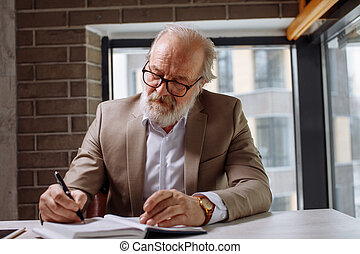 atractive experienced old man writing important information in the notepad