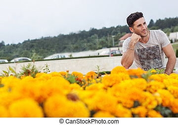 atractive man looking sideways in front of flowers