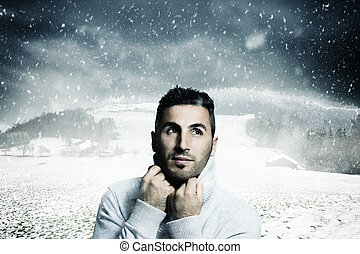 atractive man warm up with pullover and looking sideways to fallen snowflakes in front of winter landscape
