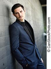 atractivo, joven, hombre de negocios, en, urbano, plano de fondo