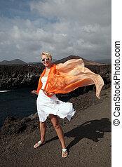 atractivo, mujer, con, vestido blanco, en, volcánico, lava, rocas