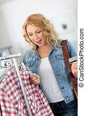 atractivo, mujer, en, tienda de ropa, precio que verifica