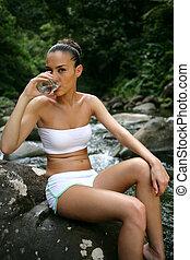 atractivo, mujer, llevando, un, biquini, y, agua potable, en, el, bosque