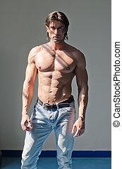atractivo, muscleman, posición, shirtless, en, gris, plano de fondo