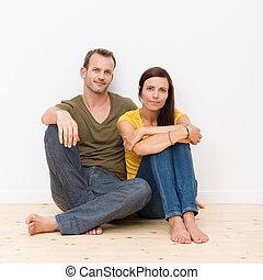 atractivo, pareja joven, sentado sobre el piso