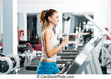 atraente, mulher jovem, corridas, ligado, um, treadmill