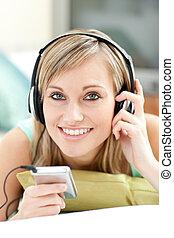 atraente, mulher jovem, escutar, música, mentindo, ligado, um, sofá