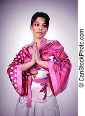 Atrractive girl in kimono pray