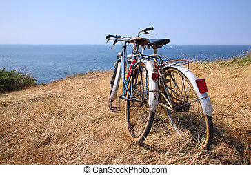 Two attached bicycles near the coast, during holidays in France.