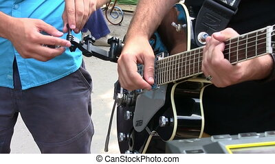 Attaching a tuner to electric guitar before live concert