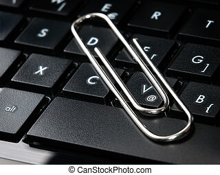 Paper clip on the keyboard as a metaphor about sending an attachment in e-mails.
