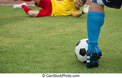 Attack soccer player shooting to defense team in football...