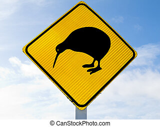 New Zealand Road Sign, Attention Kiwi Crossing against a cloudy blue sky