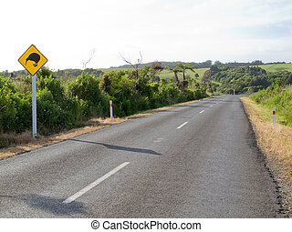 New Zealand Road Sign, Attention Kiwi Crossing beside country road warning motorist to watch out for this endangered icon of NZ
